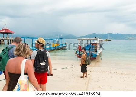 GILI MENO, INDONESIA - May 6, 2013 - Tourists boarding boat island hopping - stock photo