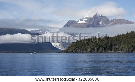 Gill net commercial fishing boat in Southeast Alaska off Seduction Point in the Lynn Canal with mountains and a glacier in the background. - stock photo