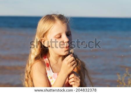 gilrl blowing on dandelion on the seashore - stock photo