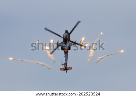 GILZE-RIJEN, NETHERLANDS - JUNE 20:Dutch Air Force AH-64 Apache in a looping firing off flares at the Royal Netherlands Air Force Days June 20, 2014 in Gilze-Rijen, Netherlands. - stock photo