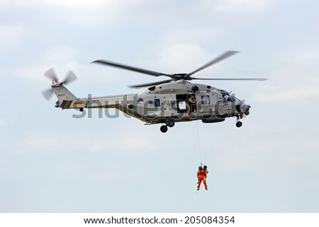 GILZE RIJEN, THE NETHERLANDS - JUNE 21:  Demonstration of a rescue operation by a Dutch Navy NH90 helicopter during  the Dutch Air Force Open House. June 21, 2014 in Gilze-Rijen, The Netherlands  - stock photo