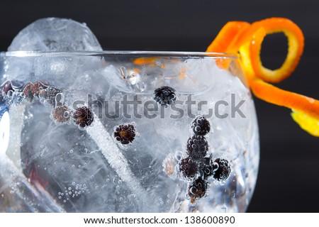 Gin tonic cocktail macro closeup with juniper berries orange - stock photo