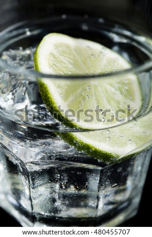 Gin tonic cocktail with lime on black background