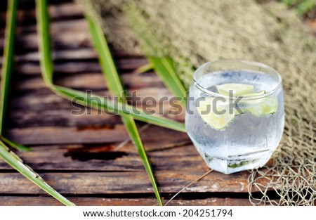 Gin tonic in glass with ice and lime slice on a wooden background with fishing net and palm leaves. Selective focus - stock photo