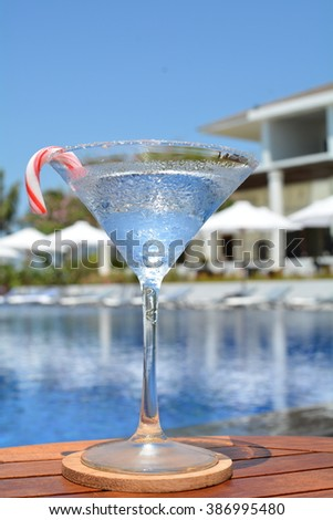 Gin Tonic Vodka Alcoholic Fresh Transparent Cocktail Drink Served in a Martini Glass decorated with a Red White Sweet Stick Set on a Wooden Surface with a Swimming Pool, White Umbrellas and Blue Sky - stock photo