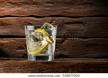 Gin tonic with lemon on wooden table and background - stock photo
