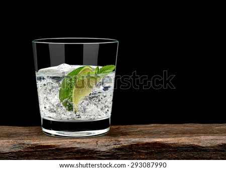 Gin tonic with lime wedge and ice in rocks glass on wooden table and black background with copy space - stock photo