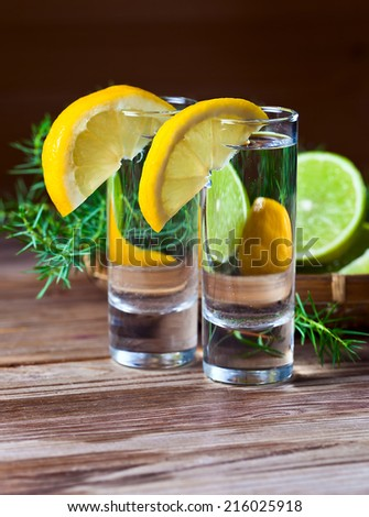 Gin with lemon on a old wooden table - stock photo