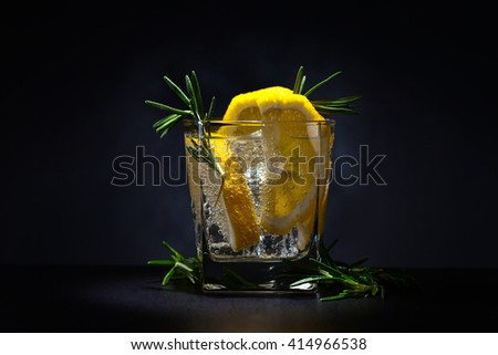 gin with tonic, lemon and rosemary on  dark background - stock photo