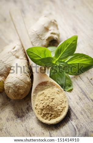 Ginger and basil on wooden table - stock photo