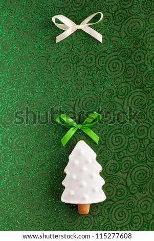Ginger and Honey cookie in the shape of a Christmas fir tree with white sugar decoration and green bow on the green texturized paper background. - stock photo