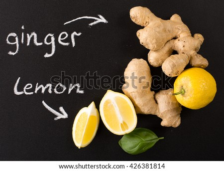 ginger and lemon on a black background - stock photo