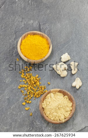 Ginger And Turmeric. Ginger powder and root  and turmeric pieces and powder in olive wood bowls over dark granite table. Macro photograph, selective focus, focus on turmeric  - stock photo