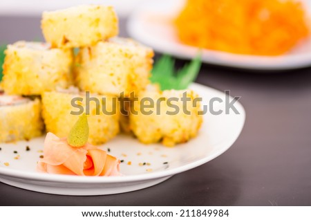 Ginger and wasabi with sushi rolls in the background selective focus - stock photo