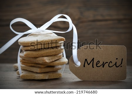 Ginger Bread Cookies with white Ribbon and Bow and Label on which the French Words Merci stands which means Thank You - stock photo