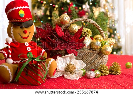 Ginger bread man dancing Christmas toy, gift box,  white flower,  red poinsettia flower, gold balls in holiday glitter basket, red tablecloth, Christmas lights bokeh background. Christmas decoration  - stock photo