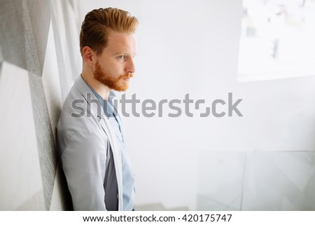 Ginger businessman in a suit in office building