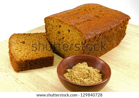ginger cake on wooden board with ginger powder - stock photo