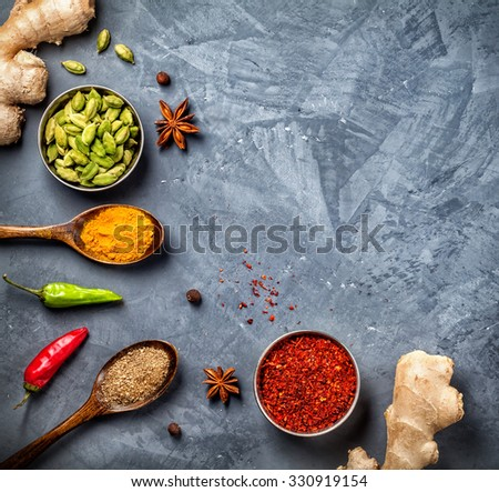 Ginger, chili peppers, cardamom, powder spices in spoons on grunge background  - stock photo