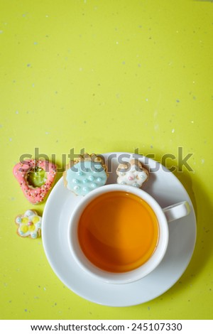 Ginger cookies and cup of tea on light green background - stock photo