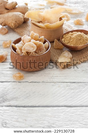 Ginger fresh root, ginger candy pieces and ginger spice on a wooden table - stock photo