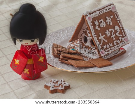 ginger gingerbread house with a wish of happiness in Japanese and Japanese doll. At house written wish of happiness - stock photo