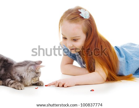 Ginger girl with a cat play with lady-beetle - stock photo