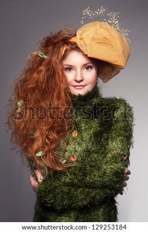 ginger lady with yellow hat and flowers on her head looking at camera - stock photo