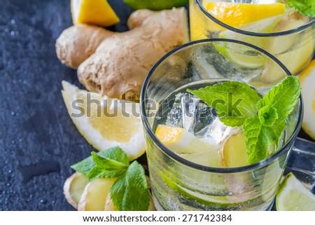 Ginger lemonade and ingredients - ginger, lemon, lime, mint, sugar, ice, dark stone background, water drops, closeup - stock photo