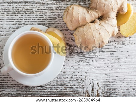 Ginger tea in a white cup on wooden background - stock photo