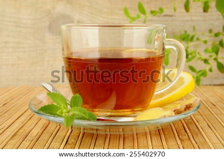 Ginger tea-ingwertee on wooden mat with lemon and mint with wooden background - stock photo