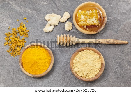 Ginger, Turmeric and honeycomb.  Ginger powder, root  and turmeric pieces, powder and honeycomb in olive wood bowls over dark granite table.  Macro photograph, selective focus - stock photo