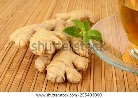 Ginger with gingertea-ingwertee on wooden mat with mint on wooden background - stock photo