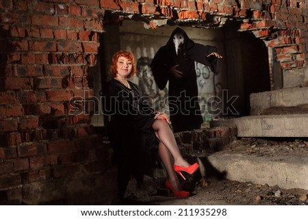 Ginger woman in black mantle with servant in abandoned building - stock photo