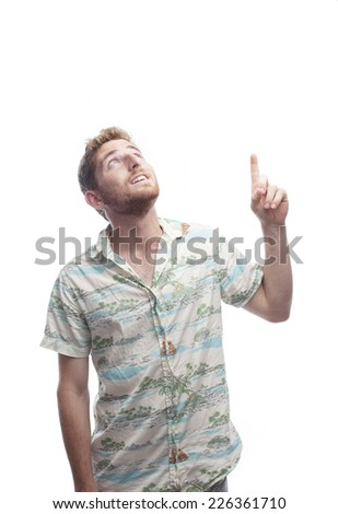 ginger young man with hawaiian shirt pointing up - stock photo