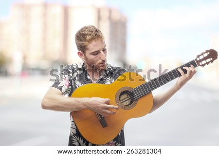 ginger young man with hawaiian shirt with a guitar - stock photo