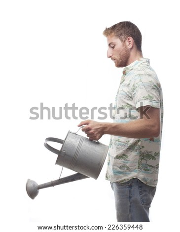 ginger young man with hawaiian shirt with a watering can - stock photo