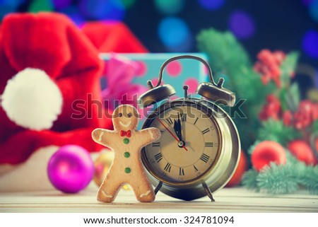 gingerbread and alarm clock with Christmas lights on background.
