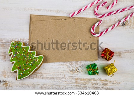 Gingerbread, candy canes and cards on a wooden background. Christmas sweets and decorations