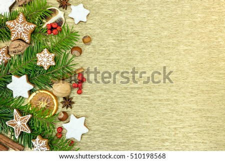 gingerbread christmas decorations with green fir-tree branches on golden background