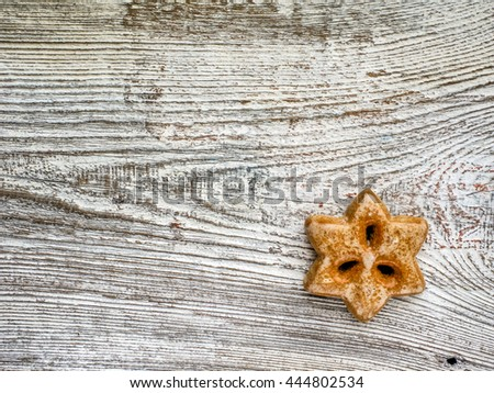 Gingerbread christmas star hanging over wooden background - stock photo