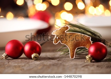 Gingerbread cookie and christmas ornaments on a table. - stock photo