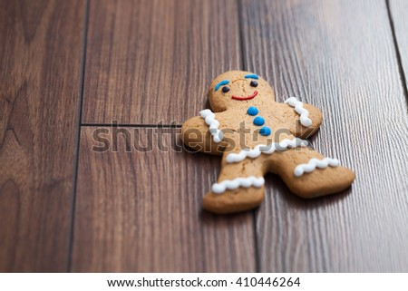 Gingerbread cookie in shape of person lying on wooden table. Smiling eatable character with good taste. Close up macro, copy space on bright dark wood surface - stock photo