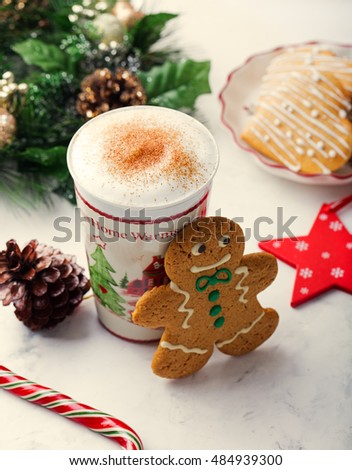 Gingerbread cookie man and  hot cup of cappuccino. Traditional Christmas dessert.