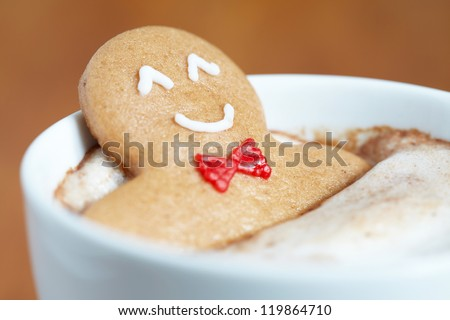 Gingerbread cookie man in a hot cup of cappuccino - stock photo