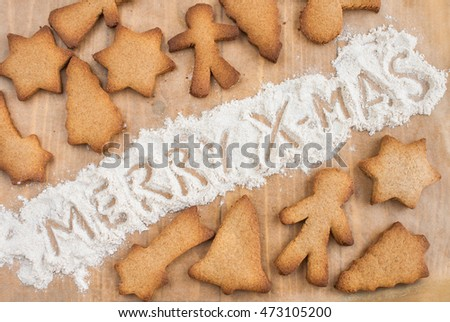 "Gingerbread cookies and ""Merry Christmas"" wishing on a baking paper. Christmas decoration concept."