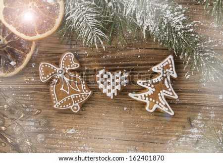 Gingerbread cookies and spices on wood plank