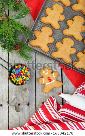 Gingerbread cookies being decorated on a raw, weathered wood background.