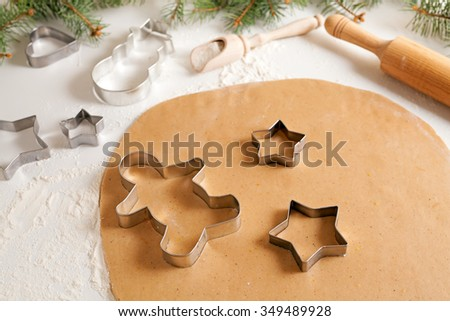 Gingerbread cookies dough preparation recipe with cinnamon rolling pin and flour on white kitchen table. Traditional homemade christmas dessert - stock photo