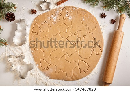 Gingerbread cookies dough preparation recipe with man shape, fir trees, snowman and star forms, cinnamon rolling pin, flour on white kitchen table. Traditional homemade christmas dessert - stock photo